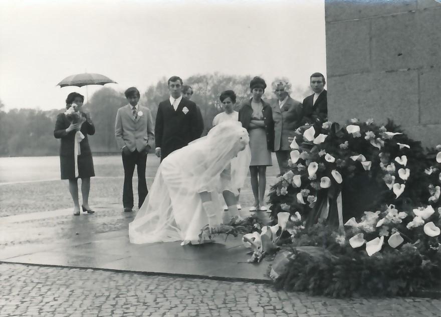 Brautpaar und Gäste vor Denkmal mit Trauerkranz